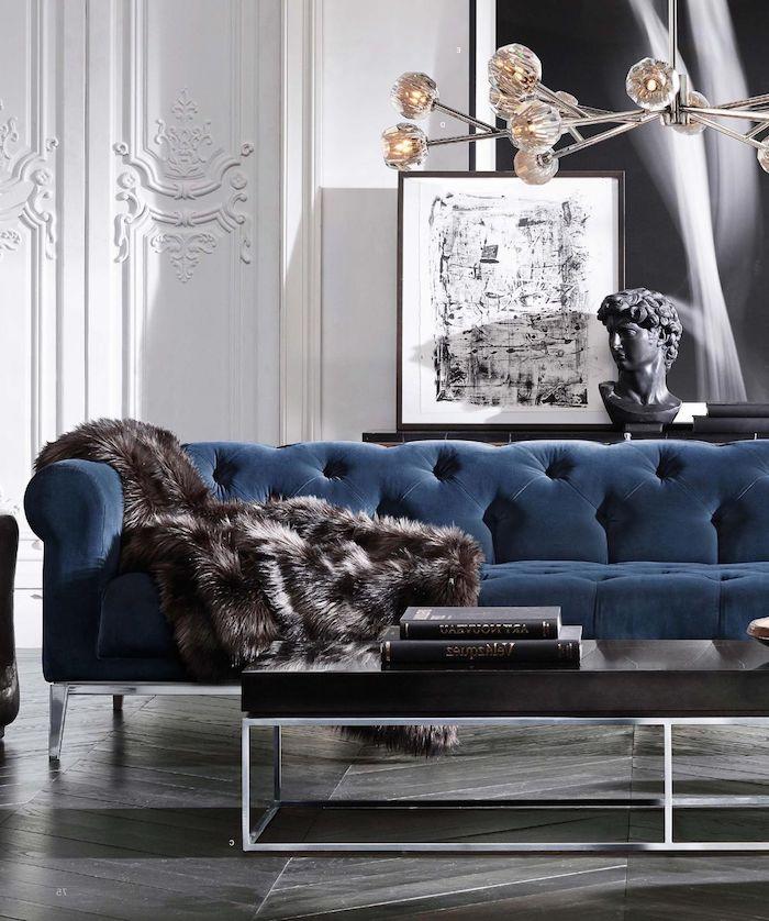 Dunkelblaues Sofa und Pelz, schwarzer Couchtisch, dunkles Parkett, Wandfarbe Weiß