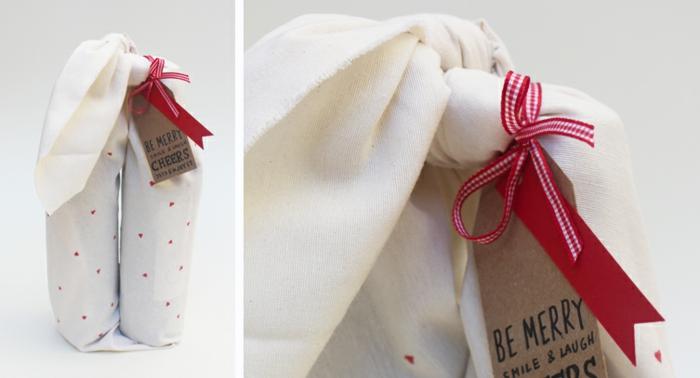 eine weiße Flascheverpackung aus Stoff mit einer rote Schleife und Glückwunsch zu Weihnachten