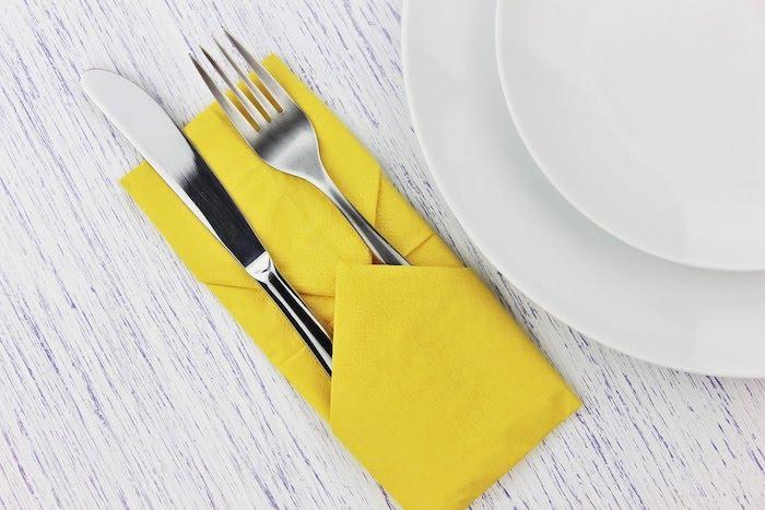 ein tisch mit einer großen gelben und gefalteten serviette und mit zwei weißen tellern, eine bestecktasche mit einem löffel und mit einem messer, ein weißer tisch aus holz, servietten falten hochzeit