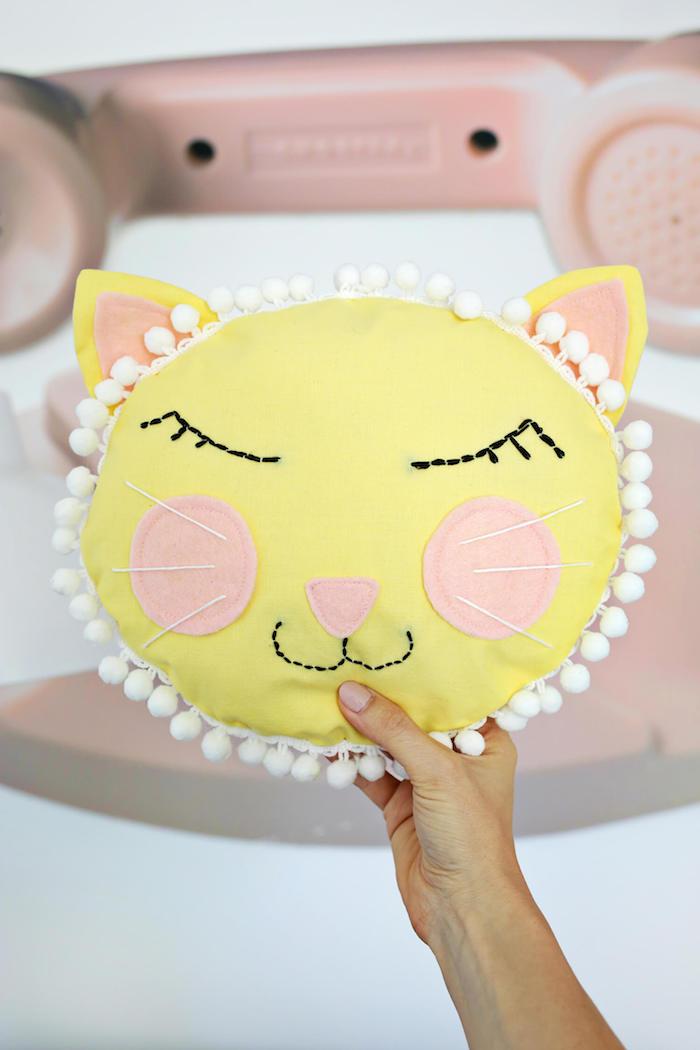 Katze Kissen selber nähen, Wangen und Nase aus rosa Stoff, mit weißen Pompons verziert