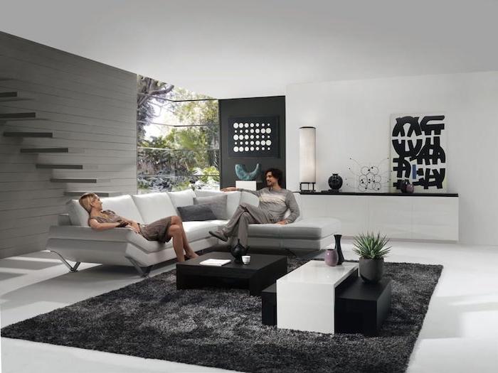 mann und frau zu hause genießen ihr graues wohnzimmer, gut beleuchtet, frische laune und atmosphäre zu hause