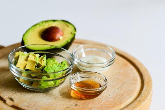 wie wachsen haare schneller, schüssel aus glas, avocadohälfte, honig, avocadowürfeln, kokosöl