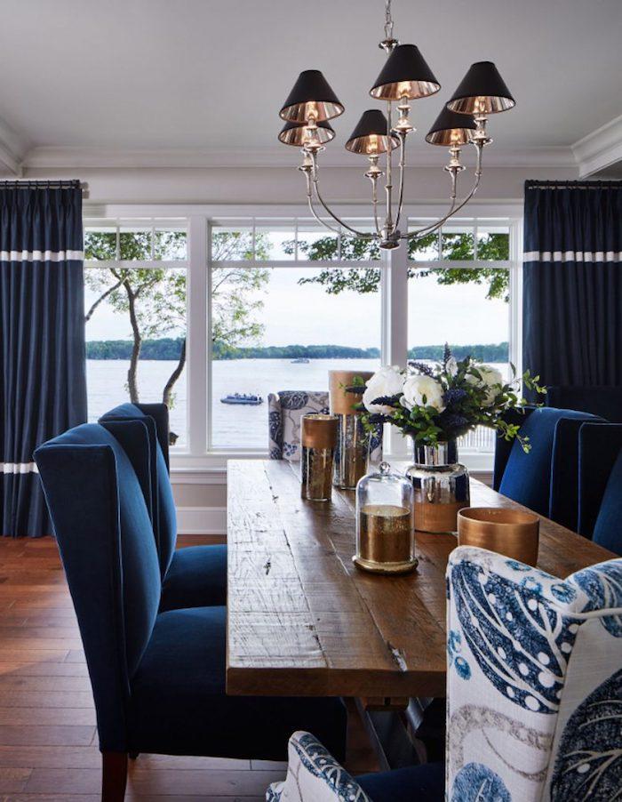 Wohnzimmer in Dunkelblau und Weiß, Tisch aus massivem Holz, blaue Vorhänge und Stühle