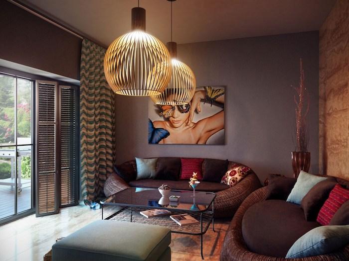 Wohnzimmer in Braun, runde Kronleuchter, viele Deko Kissen, Gemälde an der Wand, Frau und Schmetterlinge