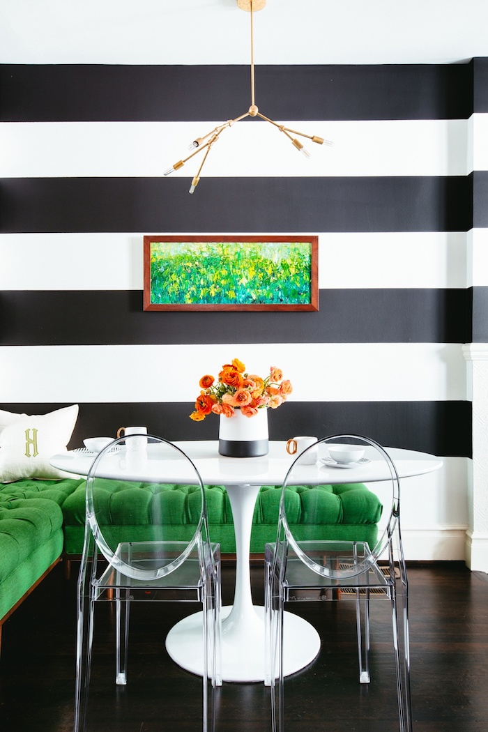 Wandfarbe Schwarz und Weiß, grünes Sofa, durchsichtige Stühle und weißer runder Tisch