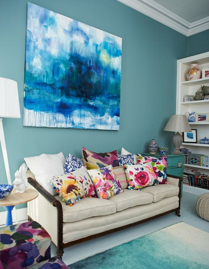 Wohnzimmer in Türkis, bunte Deko Kissen mit Blumenmuster, Gemälde an der Wand