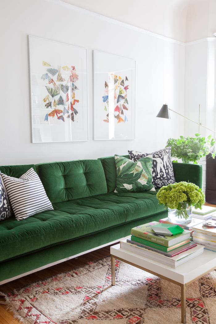 Wohnzimmer Einrichtung, dunkelgrünes Sofa, grüne Zimmerpflanzen, weißer Couchtisch