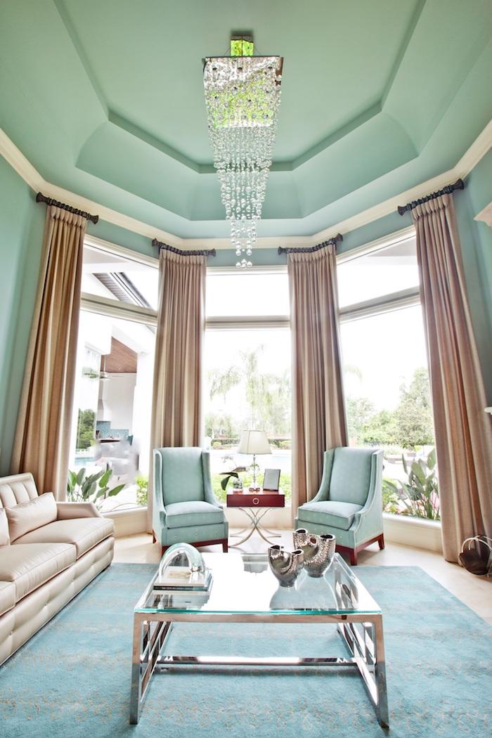 Wohnzimmer in Pastellfarben, Wandfarbe Blaugrün, Vorhänge in creme, Glas Couchtisch, Kronleuchter mit Kristallen