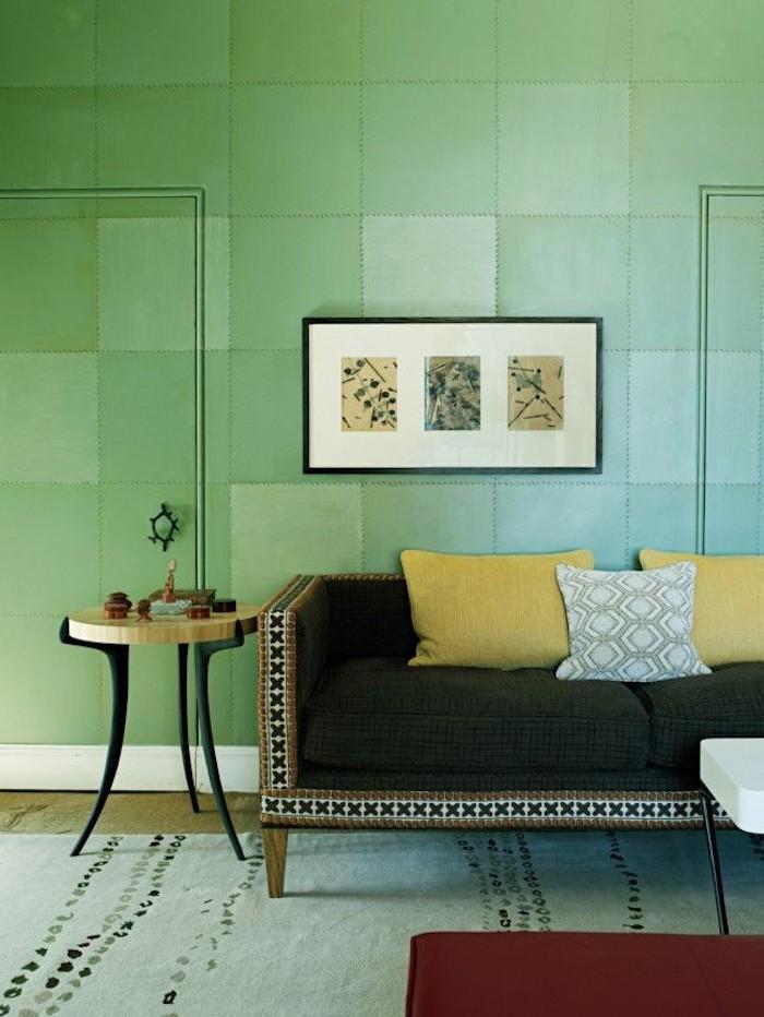 Wohnzimmer Wandfarbe Grün, schwarzes Sofa mit Deko Kissen, kleiner Couchtisch, Bilder an der Wand