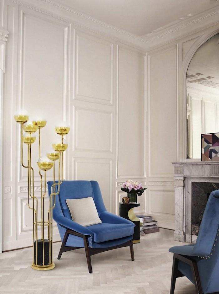 Wandfarbe Weiß, blaue Sessel, Kamin und großer Spiegel, goldene Stehlampe