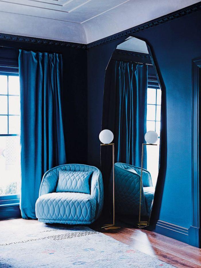 Wandfarbe Dunkelblau, großer Spiegel an der Wand, hellblauer Sessel, blaue Vorhänge