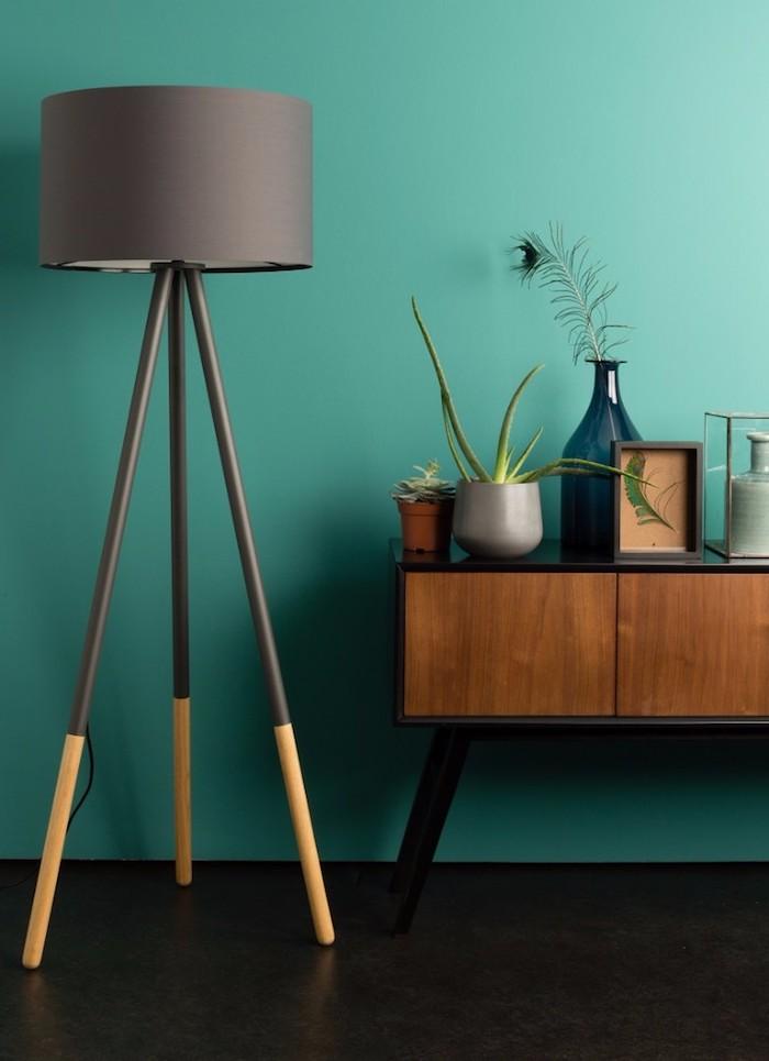 Wandfarbe Grün, schwarze Stehlampe, Vintage Nachttisch aus Holz, Pfaufeder in Glasvase, Aloe in Blumentopf