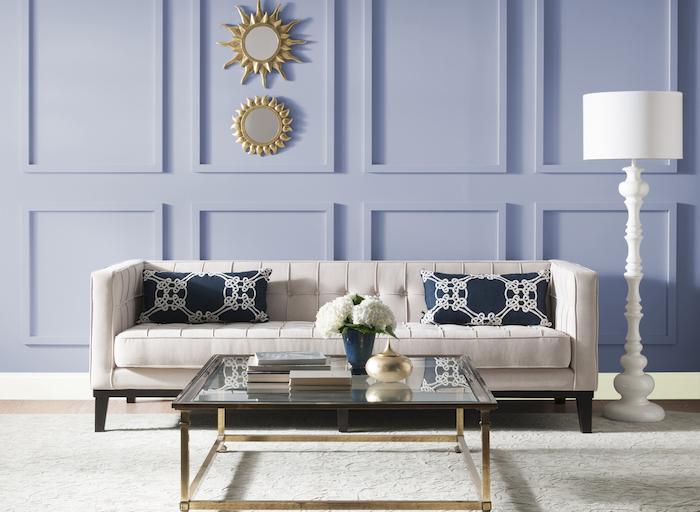 Kombination aus Blau und Weiß, Spiegel in Form von Sonnen, weißes Sofa mit dunkelblauen Deko Kissen, weiße Stehlampe