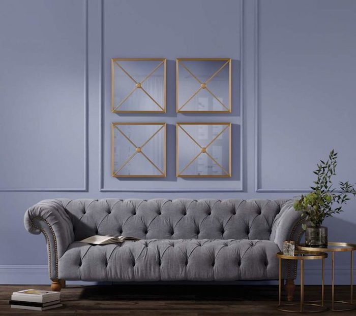 Wandfarbe Lila, graues Sofa, dunkles Parkett, Bücher auf dem Boden, Zweige in Vase