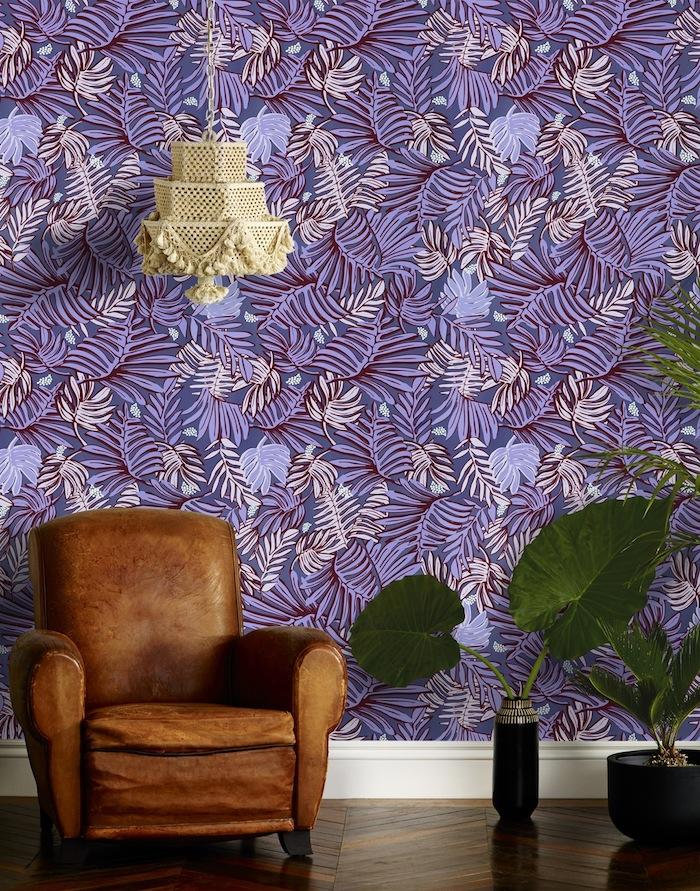 Lila Tapete mit Blumenmuster, brauner Ledersessel, grüne Zimmerpflanzen, verspielter Kronleuchter