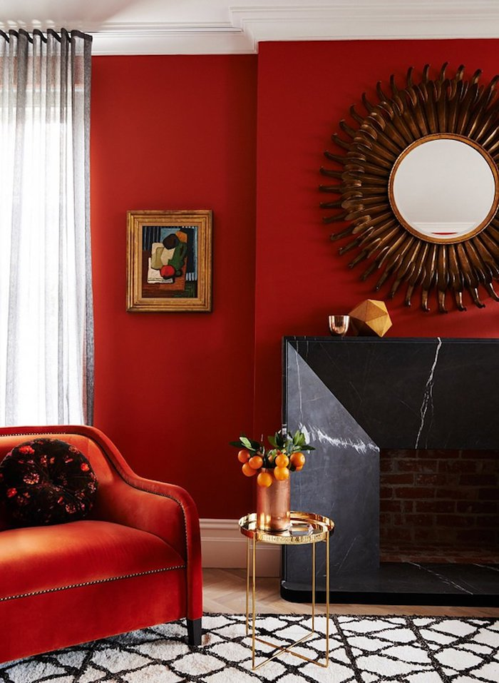 Wohnzimmer in Rot, Spiegel in Form von Sonne, roter Sessel, kleiner Tisch, weiße Vorhänge
