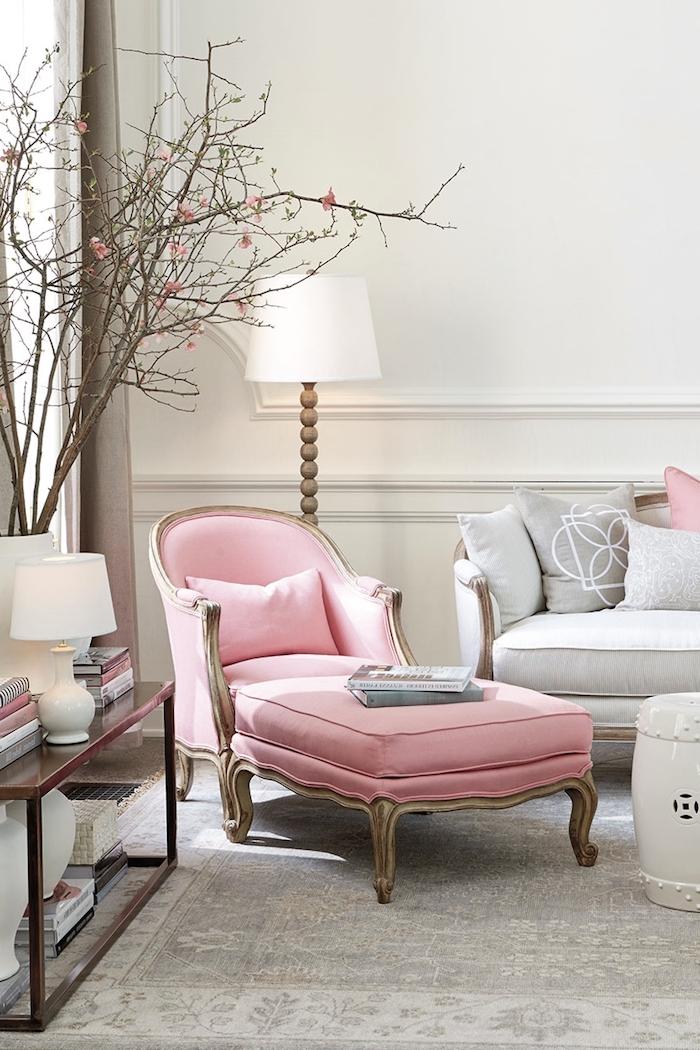 Wohnzimmer in hellen Pastellfarben, Sessel in Rosa, weißer Stehlampe, Zweige in Vase
