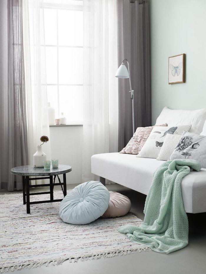 Wohnzimmer in Pastellfarben, Wandfarbe Mintgrün, weißes Sofa mit vielen Deko Kissen, kleiner Couchtisch