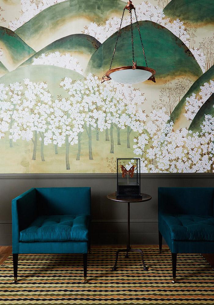 Wohnzimmer Einrichtung, blaugrüne Sessel und kleiner Holztisch, Gemälde an der Wand, Gebirge und blühende Bäume