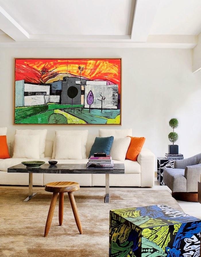 Weißes Sofa und schwarzer Couchtisch, Hocker aus Holz, Gemälde an der Wand