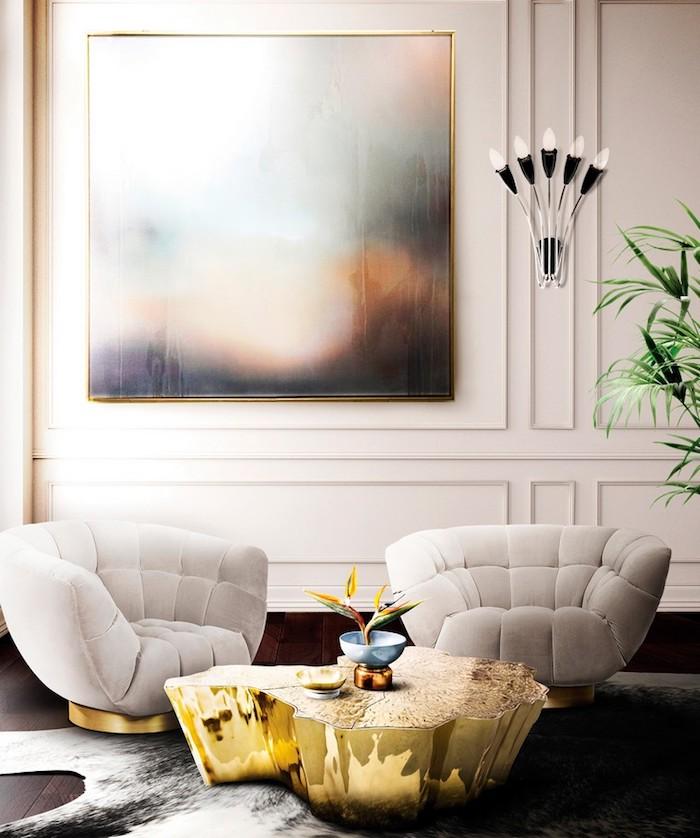 Wandfarbe Weiß, weiße Sessel, niedriger Couchtisch, Wandlampe und grüne Zimmerpflanze