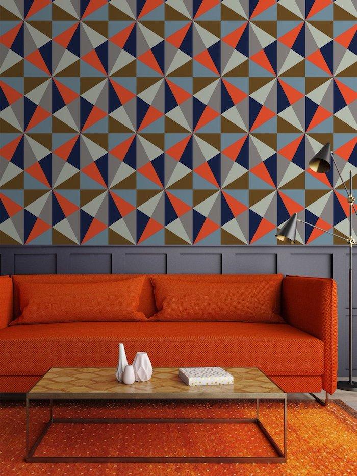 Tapete mit geometrischen Formen, rotes Sofa und niedriger Holztisch, kleine weiße Porzellanvasen