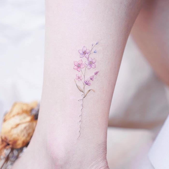Zartes farbiges Tattoo Motiv, Blume mit rosa und lila Blüten, Ideen für Bein Tattoos