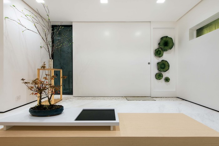 ein zimmer mit weißen wänden und mit einem kleinen weißen tisch mit einem großen baum mit langen braunen ästen, weiße lampen und grüne steine, eine wohnung einrichten