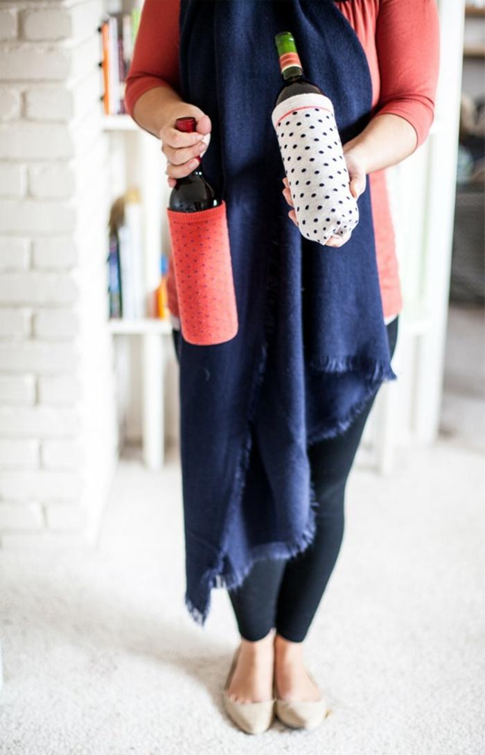eine Frau trägt Flaschen als Geschenk verpackt, Flaschen mit alten Socken verpacken