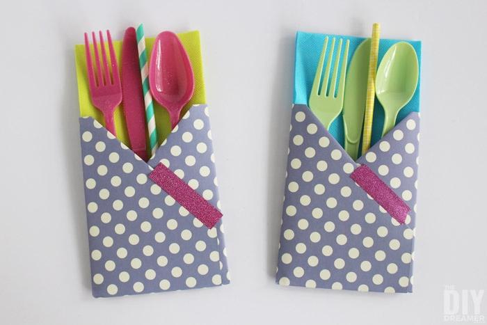 tischdeko selber basteln, zwei violette selbstgebastelte bestecktaschen mit grünen und blauen serviette, strohhalmen, violetten und grünen löffeln, messern und gabeln