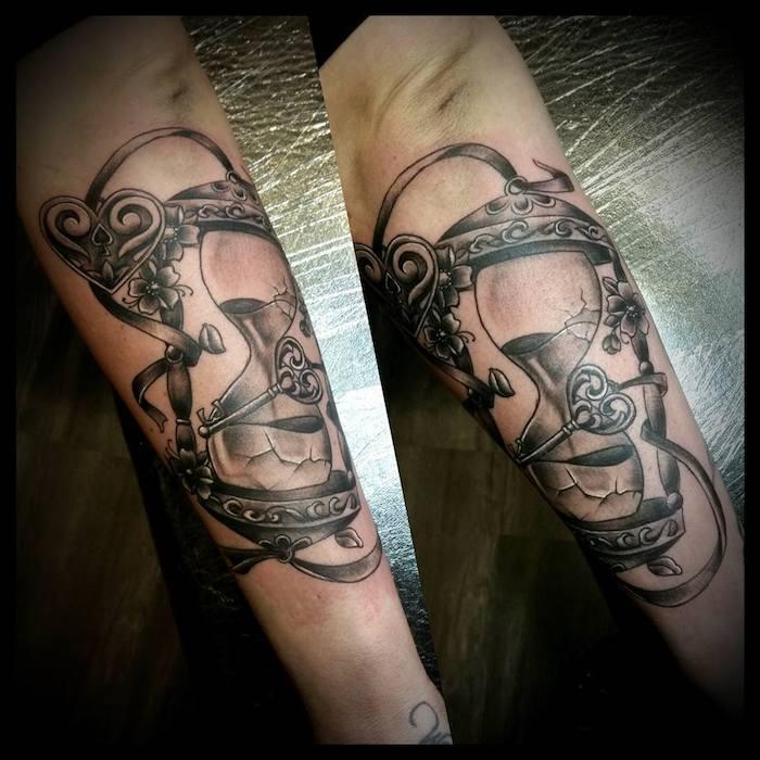zwei hände mit einem großen schwarzen tattoo mit einer schwarzen großen sanduhr und mit einem schwarzen herzen und vielen kleinen schwarzen blumen und blättern