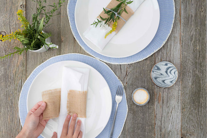 ein tisch aus holz und mit zwei weißen tellern mit weißen servietten und bestecktaschen, zwei hönde und eine gabel, gelbe pflanzen und blumen mit grünen blättern