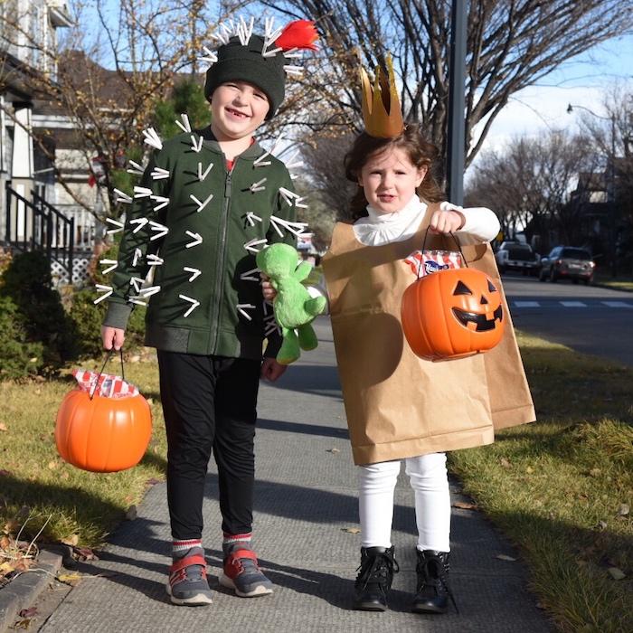 ein junge und ein mädchen mit zwei großen orangen kürbissen und kit einem grünen kaktus und mit kostümen, basteln mit papiertüten