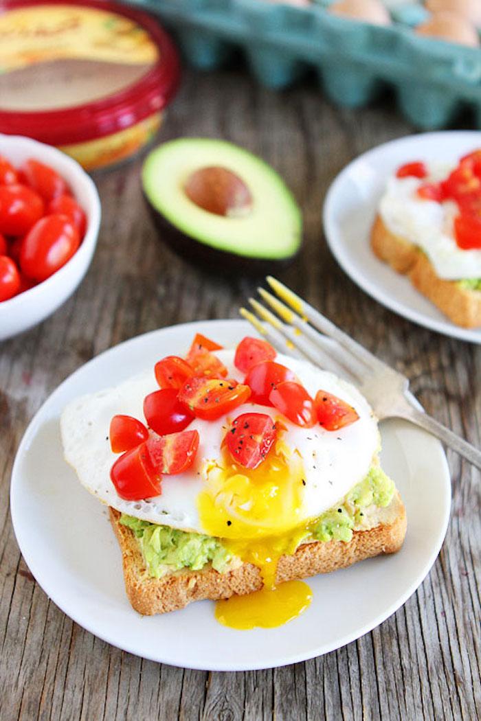 kalorienarme rezepte zum frühstücken, brotscheibe mit ei, cherry tomaten und avocadopüree