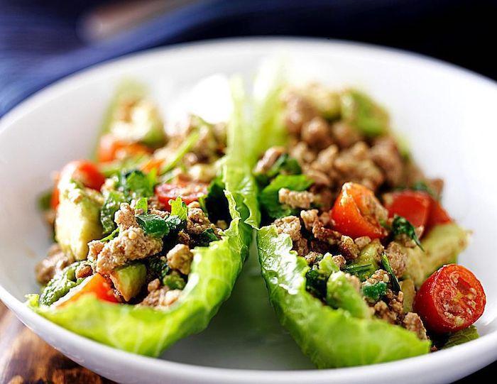 kalorienarmes essen, weißer schüssel, tacos aus grünem salat gefüllt mit hackfleisch und cherry tomaten