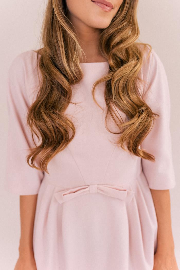 Offene lange Haare, schöne Wellen, rosa Kleid mit Schleife, matter Lippenstift