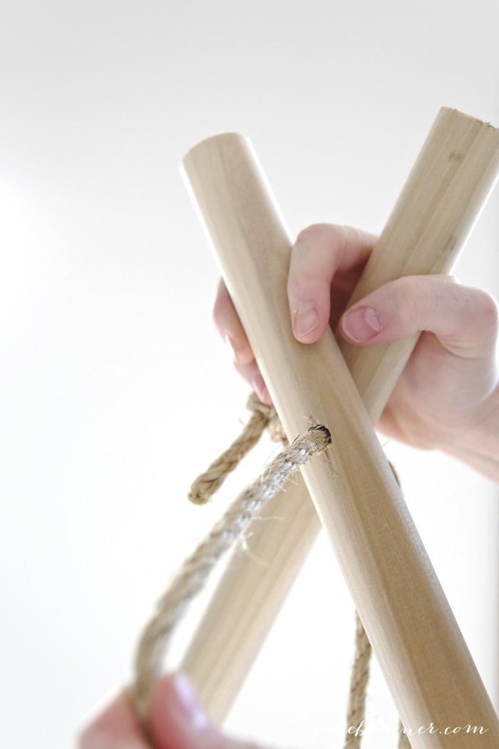 eine hand und zwei große lange stöcke aus holz, eine schnur und eine weiße wand, ein tipi selber bauen, schritt für schritt anleitung