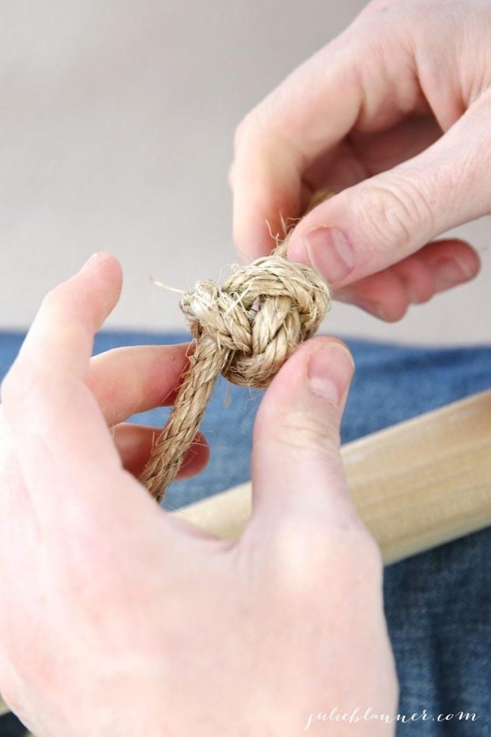 ein knoten aus einer schnur, zwei hände und ein langer stock aus holz, eine diy schritt für schritt bauanleitung, ein tipi kinderzelt selber bauen