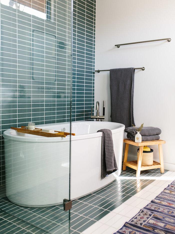 Badezimmer Einrichtung, weiße Badewanne, Fliesen in Türkis und Weiß, Hocker aus Holz, graue Handtücher