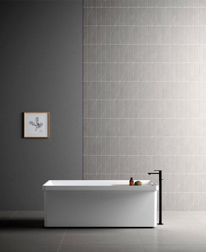 Badezimmer Einrichtung, schlichtes Design, graue Wand- und Bodenfliesen, weiße Badewanne