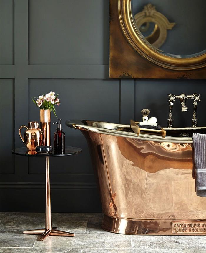 Badezimmer Einrichtung, graue Bodenfliesen, Wandfarbe Schwarz, Badewanne und Spiegelrahmen aus Kupfer