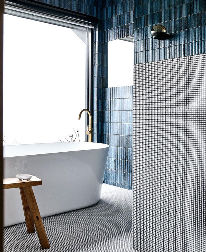 Badezimmer Einrichtung, weiße Badewanne, großes Fenster, dunkelblaue und graue Fliesen