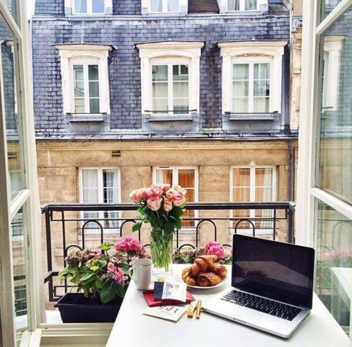 balkon einrichten ein kleiner tisch und ein stuhl sind genug, frische blumen auf dem tisch, croissants zum frühstück und laptop, den tag so anfangen