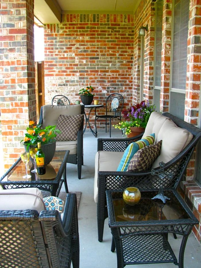 balkonmöbel kleiner balkon, langer und enger balkon, kleiner sessel, tisch mit frischen blumen darauf, schönes flair mit modernen möbeln und blumen, steinwände sind authentisch und kontrastieren mit dem eleganten einrichtungsstil