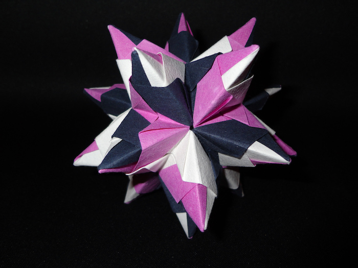 ein großer bascetta stern mit violetten, schwarzen und weißen strahlen aus papier, origami falten, basteln mit papier