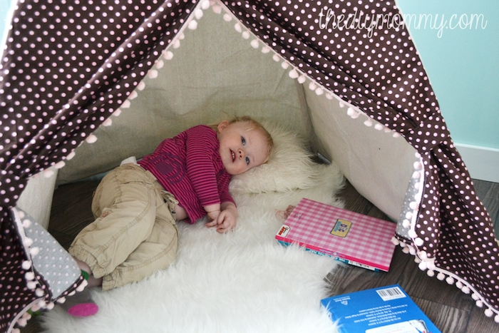 pinke und blaue bücher, ein kinderzelt tipi aus einem stoff mit vielen kleinen pinken punkten, ein kleines kind und kleine weiße kissen, kinderzimmer einrichtung