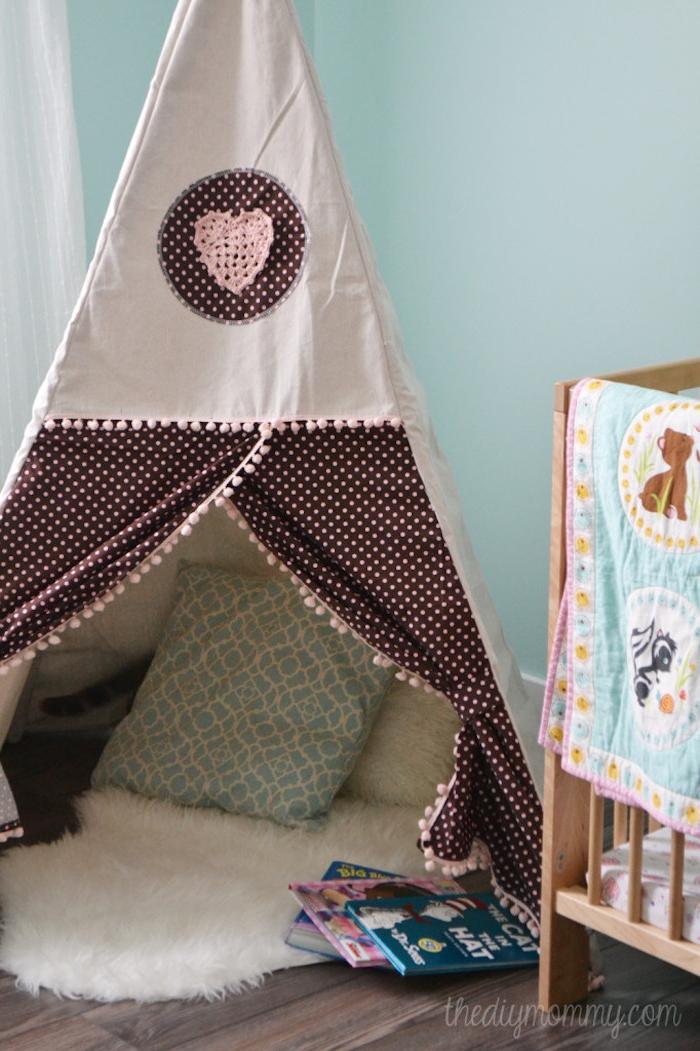 ein babybett und ein boden aus holz, ktipi kinderzimmer, ein zelt mit einem stoff mit vielen kleinen pinken punkten und mit einem großen pinken herzen und weißen und grünen kissen, drei kleine pinke und blaue kinderbücker