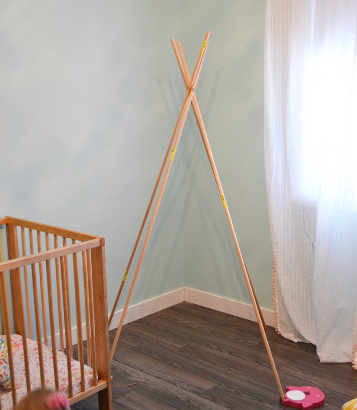 ein boden aus holz, eine kinderzimmer einrichtung, eine grüne wand und ein fenster, kinderbett tipi. eine diy schritt für schritt anleitung, vier lange stöcke aus holz, tipi selber bauen