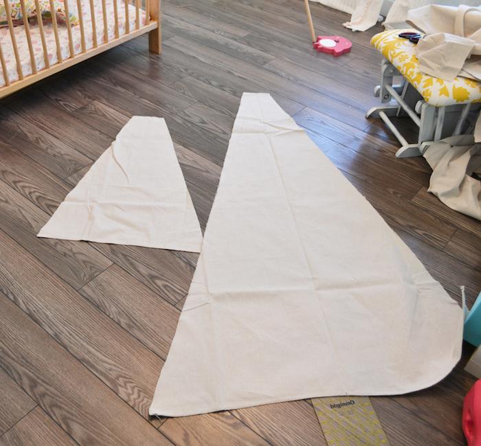 ein babybett aus holz und ein brauner boden aus holz, zwei große weiße dreiecke aus einem weißen stoff, kinderbett tipi, kinderzimmer einrichtung, tipi kinderzelt