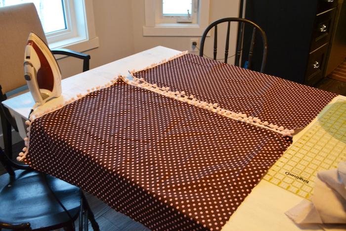 ein weißes Bügeleisen und zwei fenster, ein weißer tisch und ein stoff mit vielen kleinen pinken punkten und ein boden aus holz, kinder tipi zelt
